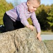 Stock Photo: Young boy clambering on rocks