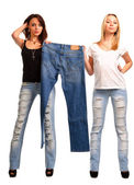 Trendy girls holding up outmoded denim jeans — Stock Photo