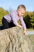 Young boy clambering on rocks — Stock Photo