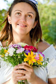 Smiling happy woman holding a floral bouquet — Stock Photo