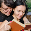 Two close woman friends enjoying a book — Stock Photo