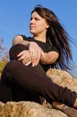 Atractiva mujer sentada sobre una roca — Foto de Stock
