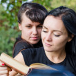 Two women reading a book together - Stock Photo