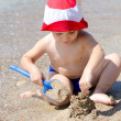 Постер, плакат: Little boy building sand castles