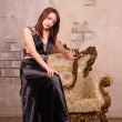 Young woman sitting on the arm of a fancy chair — Stock Photo