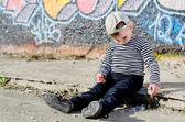 Lonely little boy sitting on the sidewalk — Stock Photo