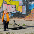 Stock Photo: Cute little boy playing in front of graffiti