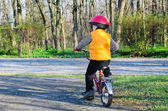 Little boy riding away from the viewer — Stock Photo