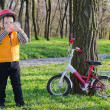 Stock Photo: Thirsty little boy drinking water while out riding