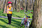 Cute little boy with his bike in woodland — Stock Photo