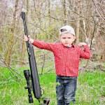 Cute little boy holding a big rifle — Stock Photo #25594589