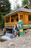 Man sitting at a wooden cabin on a waterfall — Stock Photo