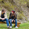 Couple chatting outdoors sitting on a wood bench — Stock Photo
