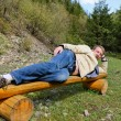 Young blond man laying on his side on a bench — Stock Photo