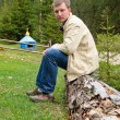 Stock Photo: Man sitting on an old tree trunk