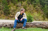 Young man sitting on a tree trunk in nature — Stock Photo