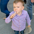 Young handsome little boy eating a treat — Stock Photo