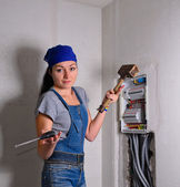 Woman with an electrical box, mallet and hammer — Stock Photo