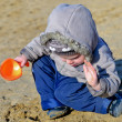 Cute child playing on the wet beach sand — Stock Photo