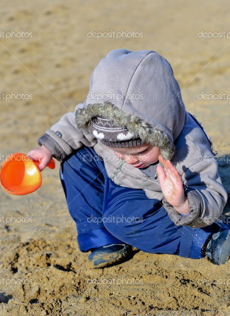 可爱小孩湿的海滩的沙子上玩