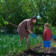 Little boy helping his mother in the garden — Stock Photo