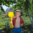 Foto de Stock  : Young boy with his spade in garden
