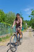 Woman riding a bicycle down a rural lane — Stock Photo