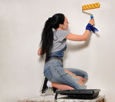 Young woman painting with a roller — Stock Photo