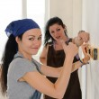 Womgiving thumbs up while renovating — Stock Photo #27776295
