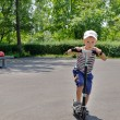 Young boy riding scooter in park — Stock Photo #28141049