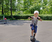 Young boy riding a scooter in a park — Stock Photo