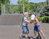 Twee jonge jongens vechten over een scooter — Stockfoto