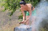 Mujer atractiva cocinar carnes en una barbacoa — Foto de Stock