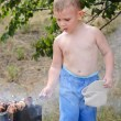 Little boy turning kebabs over the fire — Stock Photo