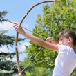 Teenage girl taking aim with a bow and arrow — Photo