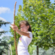 Young girl practising with a bow and arrow — Foto de Stock