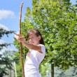 Young girl practising with a bow and arrow — Stok fotoğraf