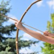 Teenage girl taking aim with a bow and arrow — Stockfoto