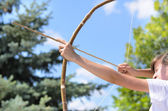 Teenage girl taking aim with a bow and arrow — Stock Photo