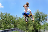 Teenage girl jumping in the air on rollerblades — Stockfoto