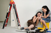 Exhausted female friends doing renovations — Stock Photo