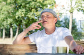 Man sitting outdoors smoking — Stock Photo