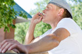 Trendy young man enjoying a smoke break — Stock Photo
