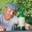 Depressed man looking at a bottle of white wine — Stock Photo