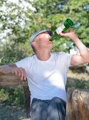 Man drinking alcohol from a bottle — Stock Photo