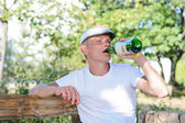 Alcoholic drinking from a bottle of spirits — Stock Photo