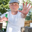 Smiling drunk defending his bottle of alcohol — Stock Photo #30543679