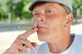 Thoughtful middle-aged man smoking in the park — Stock Photo