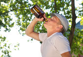 Mman drinking alcohol from a bottle, in the park — Stock Photo