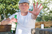 Smiling drunk defending his bottle of alcohol — Stock Photo